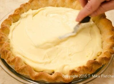 Spreading pastry cream over bananas for Double Banana Caramel Cream Pie